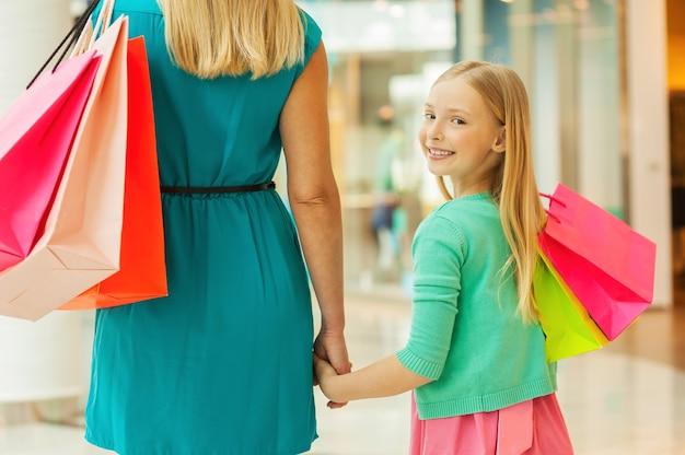 작은 쇼핑 중독자. 어린 소녀가 어깨 너머로 보고 웃고 있는 동안 쇼핑백을 들고 있는 엄마와 딸의 뒷모습