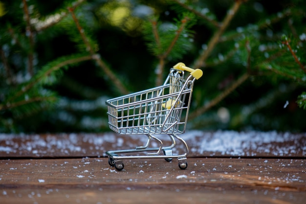 Little shopping cart on wooden table with pine and snow