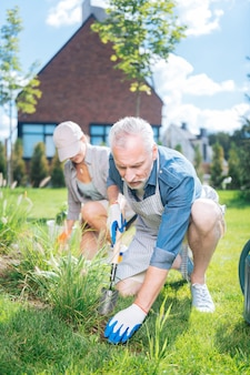 Little shovel. bearded mature man wearing striped apron holding little shovel while grubbing the weeds up