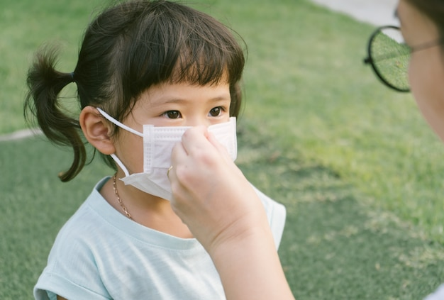 Little sian girl and  mother wearing mask for protect pm2.5 and coronavirus.air pollution pm2.5 and coronavirus concept