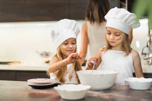 Little siblings in chef hat mixing ingredients in bowl on kitchen worktop