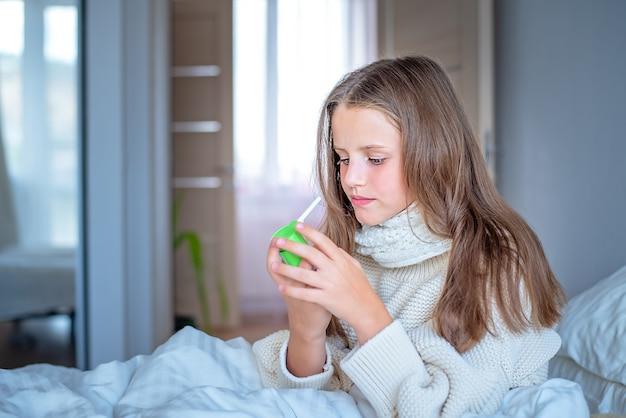 Маленькая больная девочка смотрит на спрей для горла.