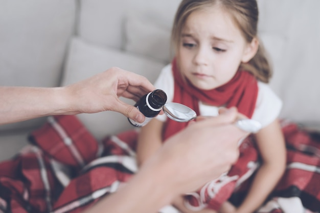 Little sick girl takes a medicine on a couch.