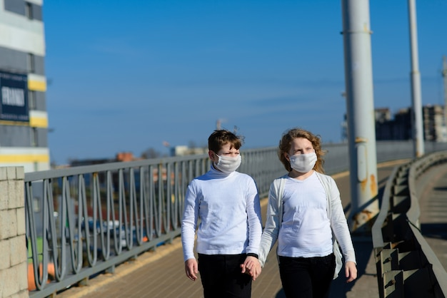 Маленькая сестра и брат в повседневной одежде и защитных масках в парке готовы к учебе в школе