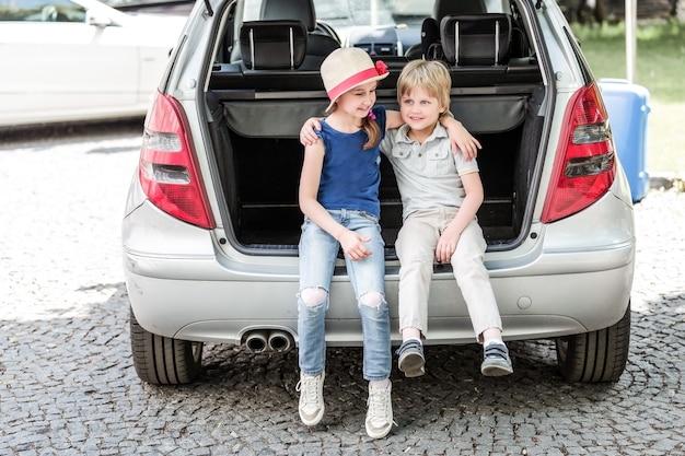 Младшая сестра и брат сидят в багажнике машины с чемоданами. концепция семейного путешествия