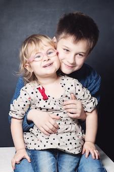 Маленькая сестра и брат улыбается
