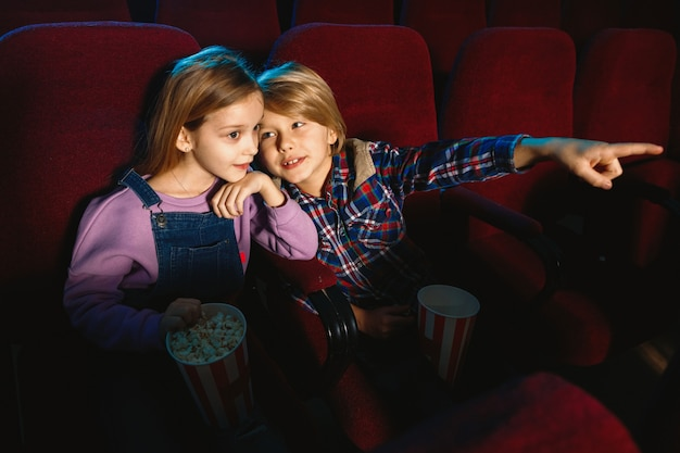 Little sister and brother watching a film at movie theater