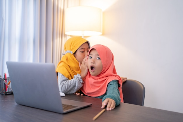 Little sister whispering something to her sibling and shocked while using laptop at home