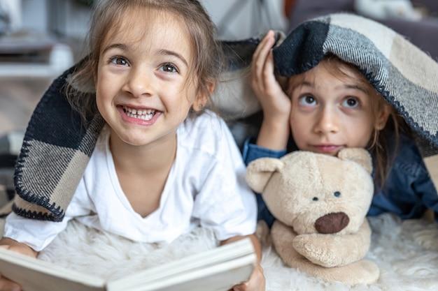 Сестрички читают книгу с плюшевым мишкой, лежащим на полу в комнате.