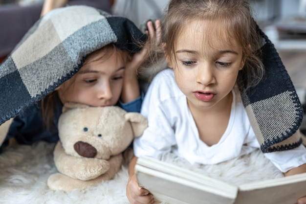 Little sisters are reading a book with a teddy bear lying on the floor in the room.