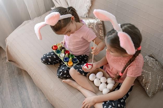 Piccole sorelle in orecchie da coniglio dipingono le uova di pasqua sul divano di casa