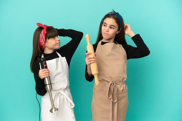 Маленькие сестры готовят дома, изолированные на синем фоне, сомневаясь, почесывая голову