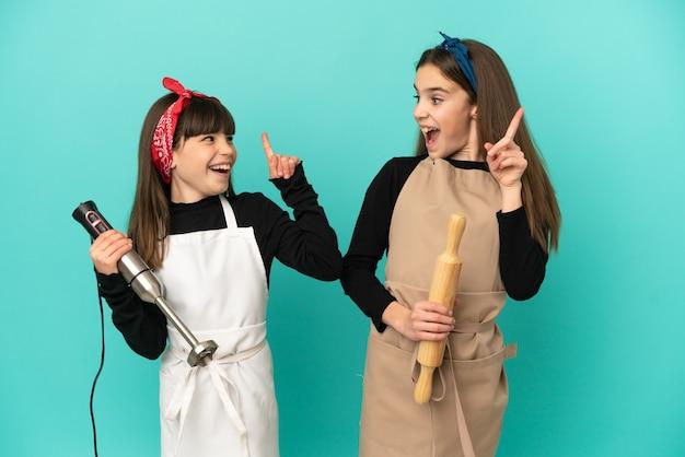 Маленькие сестры готовят дома, изолированные на синем фоне, намереваясь реализовать решение, подняв палец вверх
