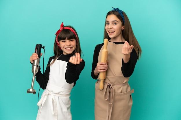 Маленькие сестры готовят дома, изолированные на синем фоне, приглашая прийти с рукой. счастлив что ты пришел