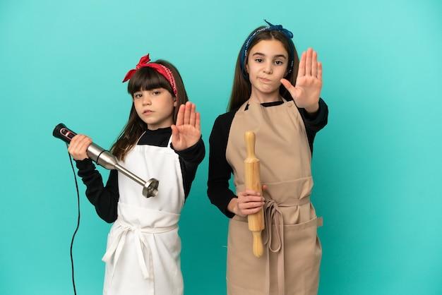 Маленькие сестры готовят дома, изолированные на синем фоне, делая жест стоп, отрицая ситуацию, которая думает неправильно