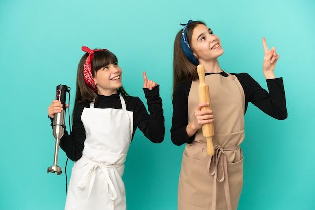 집에서 집에서 요리하는 어린 자매들은 파란 배경에 격리되어 검지 손가락으로 좋은 아이디어를 가리키고 있습니다