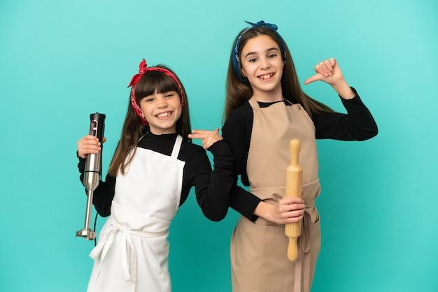 Маленькие сестры готовят дома, изолированные на синем фоне, гордые и самодовольные в любви к себе