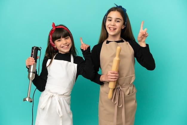 Маленькие сестры готовят дома, изолированные на синем фоне, показывая и поднимая палец в знак лучших