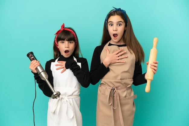 Маленькие сестры готовят дома, изолированные на синем фоне, удивлены и шокированы, глядя вправо