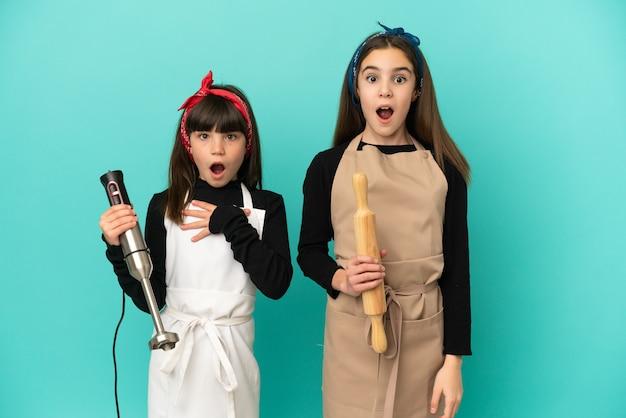 Маленькие сестры готовят дома, изолированные на синем фоне с удивленным и шокированным выражением лица