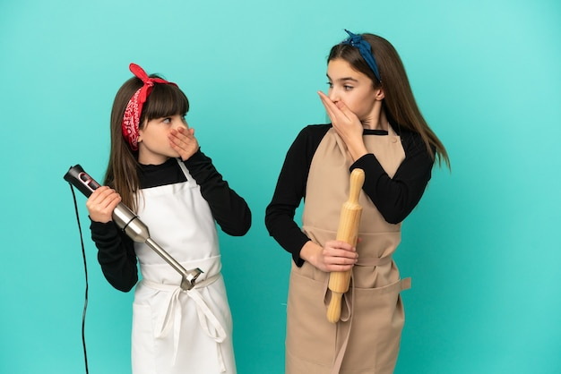 Little sisters cooking at home isolated on blue background covering mouth with hands for saying something inappropriate