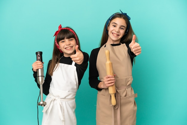 Little sisters cooking at home isolated on blue background giving a thumbs up gesture because something good has happened