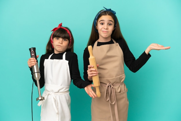 Little sisters cooking at home isolated on blue background having doubts while raising hands and shoulders