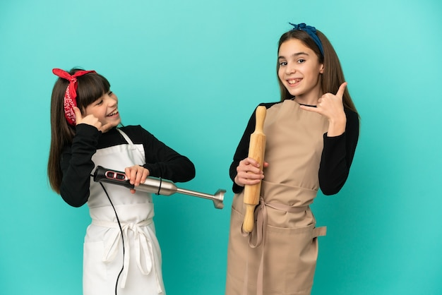 Little sisters cooking at home isolated on blue background making phone gesture. call me back sign