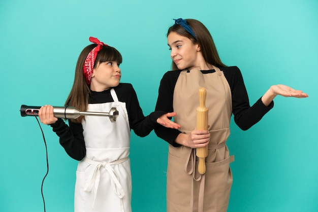 Little sisters cooking at home isolated on blue background making unimportant gesture while lifting the shoulders