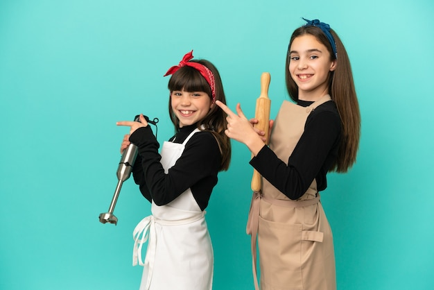 Little sisters cooking at home isolated on blue background pointing finger to the side in lateral position