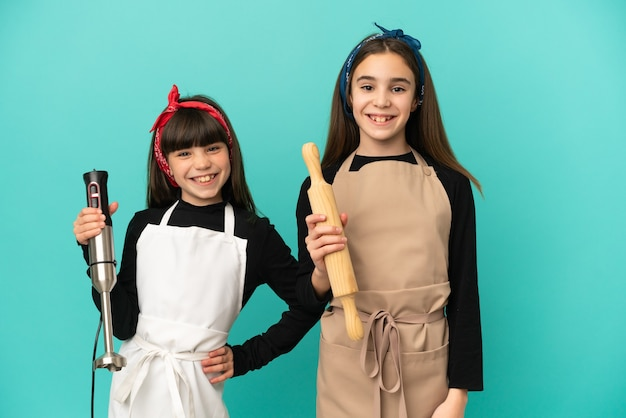 Little sisters cooking at home isolated on blue background posing with arms at hip and smiling