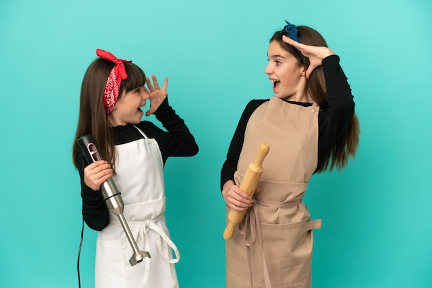 Little sisters cooking at home isolated on blue background with surprise and shocked facial expression