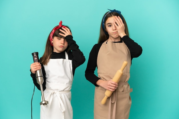 Little sisters cooking at home isolated with surprise and shocked facial expression