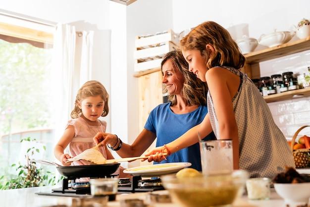 Маленькие сестры готовят вместе с матерью на кухне. концепция младенческого шеф-повара.