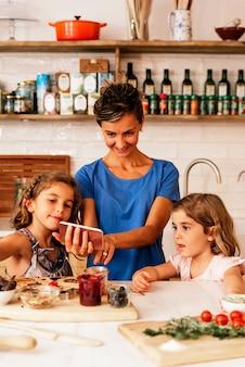 부엌에서 어머니와 함께 요리하는 어린 자매들. 유아 요리사 개념입니다.