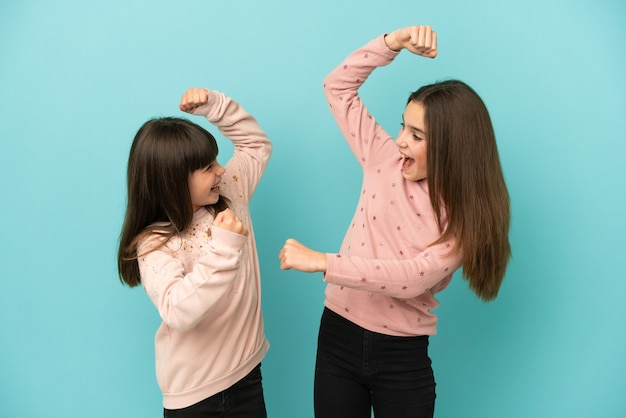 Little sisters girls isolated on blue background celebrating a victory in winner position