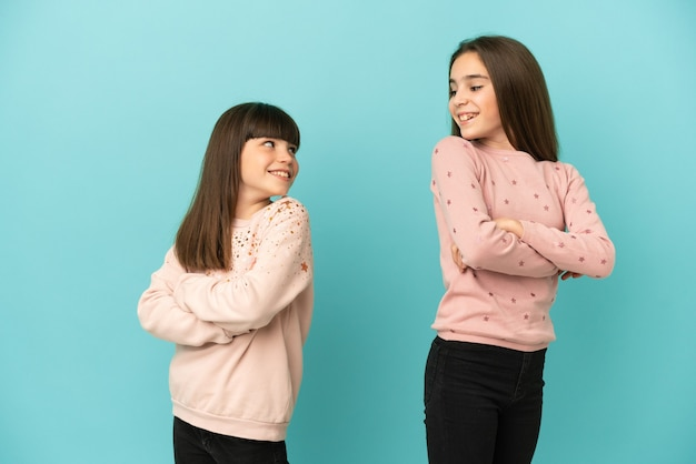 Little sisters girls isolated on blue background looking over the shoulder with a smile