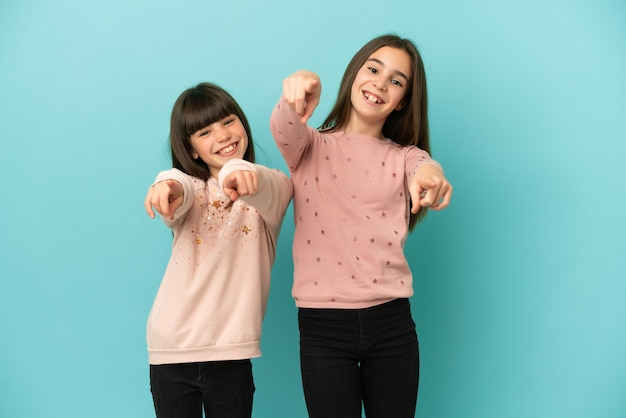 Little sisters girls isolated on blue background points finger at you while smiling