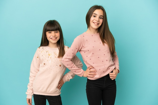 Little sisters girls isolated on blue background posing with arms at hip and smiling