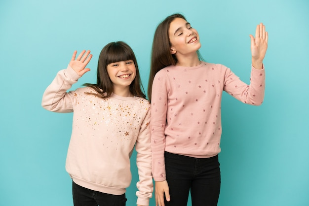 Little sisters girls isolated on blue background saluting with hand with happy expression
