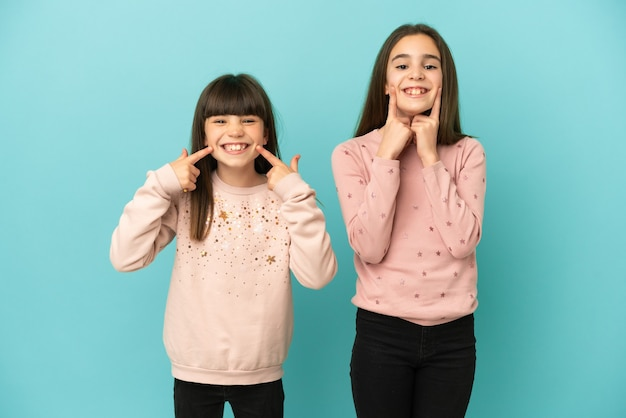 Little sisters girls isolated on blue background smiling with a happy and pleasant expression