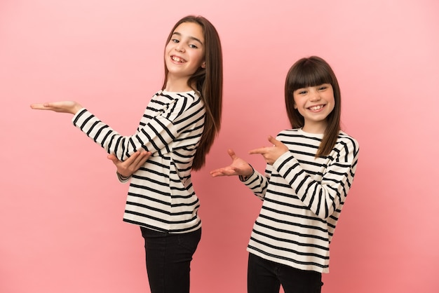 Little sisters girls isolated extending hands to the side for inviting to come