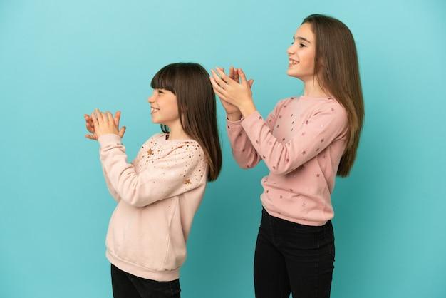 Маленькие сестры девочки изолированы на синем фоне аплодируют после презентации на конференции