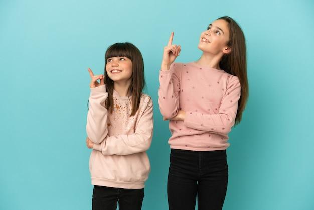 素晴らしいアイデアを指し、見上げる青い背景に分離された妹の女の子
