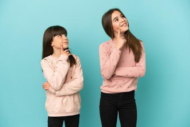 찾는 동안 아이디어를 생각하는 파란색 배경에 고립 된 여동생 소녀