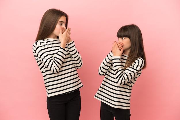 Маленькие сестры девочки изолированы на розовом фоне, закрывая рот руками за то, что говорят что-то неуместное