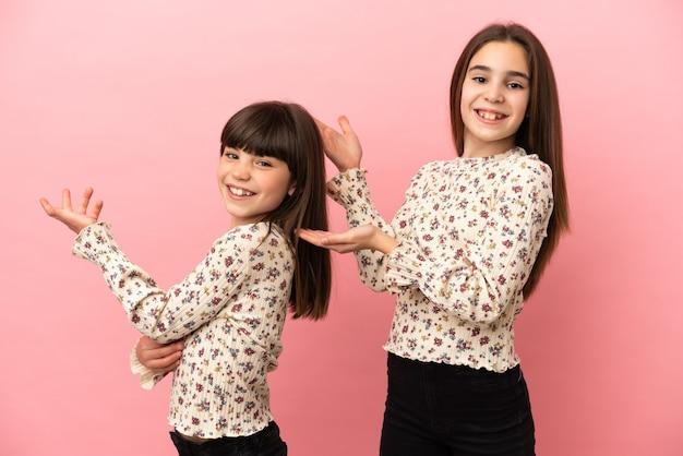 Маленькие сестры девочки изолированы на розовом фоне, протягивая руки в сторону, приглашая прийти