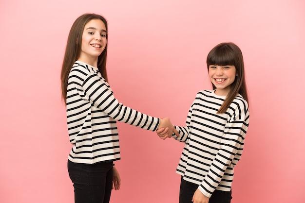 Маленькие сестры девочки, изолированные на розовом фоне, рукопожатие после хорошей сделки