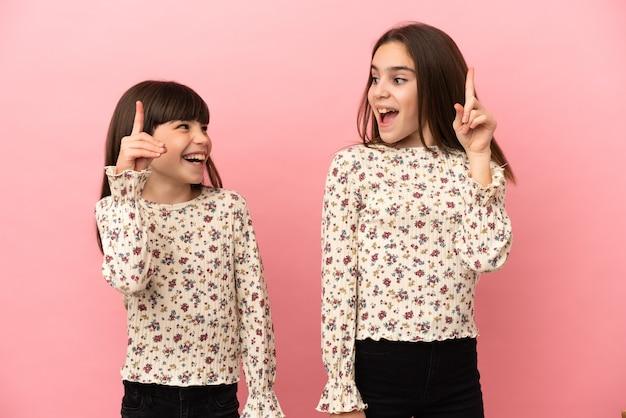 Маленькие сестры девочки изолированы на розовом фоне, намереваясь понять решение, подняв палец вверх