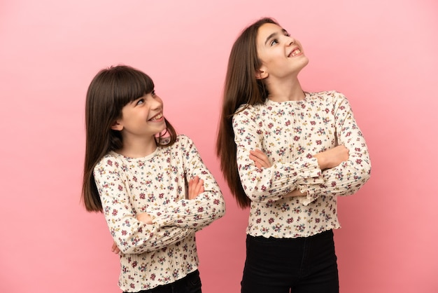 Маленькие сестры девочки, изолированные на розовом фоне, глядя вверх, улыбаясь